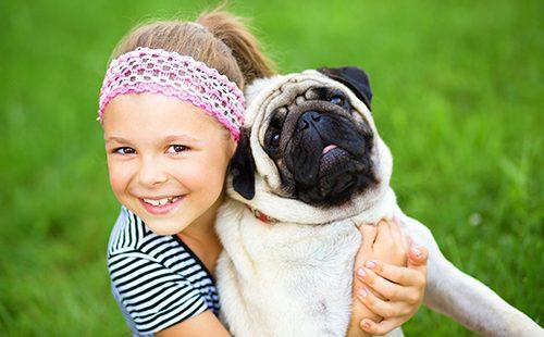 Девочка обнимает мопса