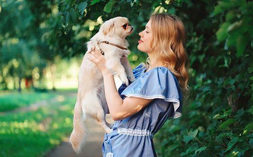 Девушка держит собачку на весу